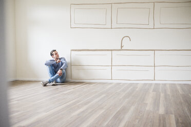 Young man in new home sitting on floor thinking about interior design - UUF10818