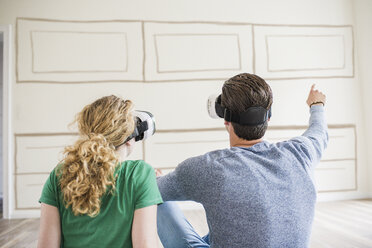 Young couple in new home wearing VR glasses thinking about interior design - UUF10821