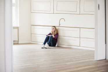 Young woman in new home sitting on floor thinking about interior design - UUF10824