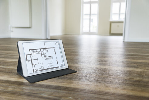 Tablet with floor plan on wooden floor - UUF10827