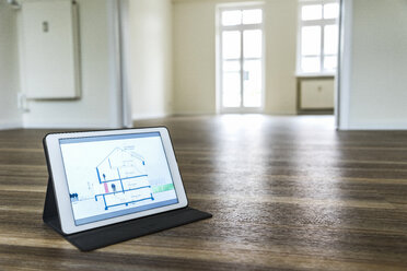 Tablet with house model on wooden floor - UUF10830
