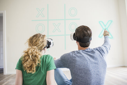 Young couple wearing VR glasses playing virtual tic tac toe - UUF10833