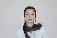 Portrait of a young woman wearing her ponytail wrapped around her neck - JOSF01115