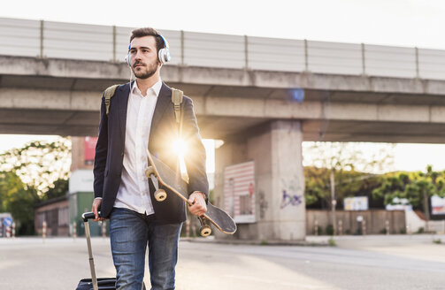 Young man on the move with skateboard, rolling suitcase and headphones - UUF10835