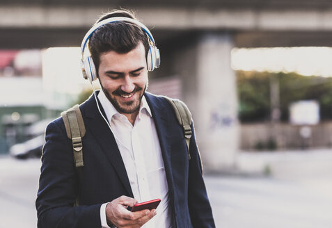 Smiling young man owearing headphones checking cell phone - UUF10838