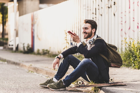 Smiling young man sitting on pavement using cell phone - UUF10844