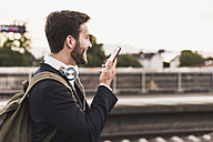 Smiling young man using cell phone on platform - UUF10853