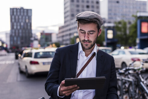 Young man in the city with tablet - UUF10856