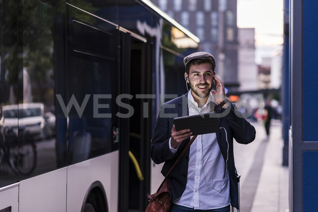 Young man at the bus stop in the city with earphones and tablet - UUF10859 - Uwe Umstätter/Westend61