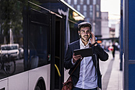 Young man at the bus stop in the city with earphones and tablet - UUF10859