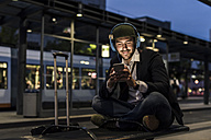 Young man in the city with headphones and cell phone in the evening - UUF10865