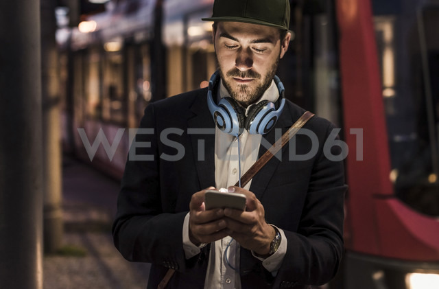 Young man in the city checking cell phone in the evening - UUF10868 - Uwe Umstätter/Westend61