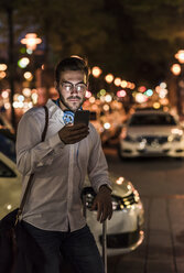 Young man in the city checking cell phone at night - UUF10871