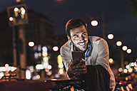 Smiling young man in the city with cell phone at night - UUF10874