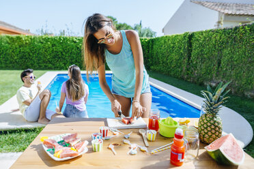 Woman preparing watermelon juice at the poolside with friends in background - KIJF01511