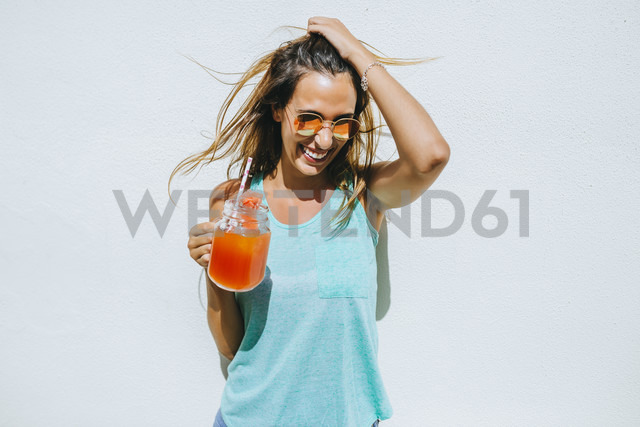 Happy young woman holding watermelon drink in front of white wall - KIJF01514