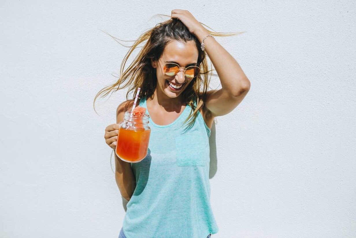 Happy young woman holding watermelon drink in front of white wall - KIJF01514 - Kiko Jimenez/Westend61