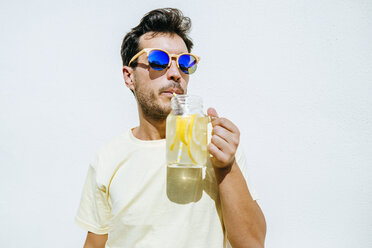 Man with sunglasses drinking lemonade in front white wall - KIJF01517