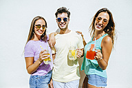 Happy friends holding refreshing drinks in front of white wall - KIJF01520