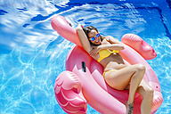 Carefree young woman on pink flamingo float in swimming pool - KIJF01523