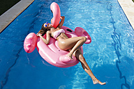 Carefree young woman on pink flamingo float in swimming pool - KIJF01529