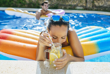 Young woman in swimming pool with drink at the poolside - KIJF01532