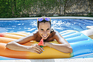 Portrait of happy young woman on airbed in swimming pool - KIJF01535
