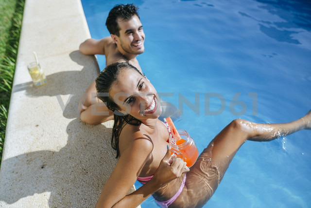 Happy couple in swimming pool with drink at the poolside - KIJF01538