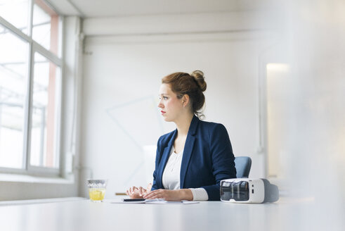 Businesswoman sitting at desk with VR goggles - JOSF01138