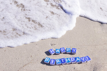 Letters on match boxes building the word 'Happy Birthday' on the beach - CMF00684