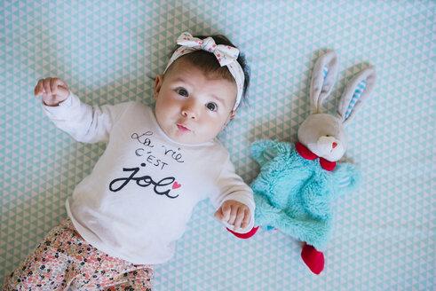 Baby girl lying on bed beside toy bunny - GEMF01667