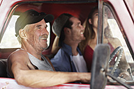 Happy senior man and young couple in an old pick up - ZEF13884