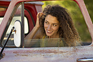 Happy young woman fixing her hair in car miror - ZEF13887
