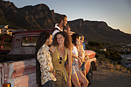 Young people outside pick up truck at the coast enjoying the sunset - ZEF13917