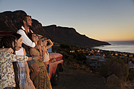 Young people outside pick up truck at the coast enjoying the sunset - ZEF13920