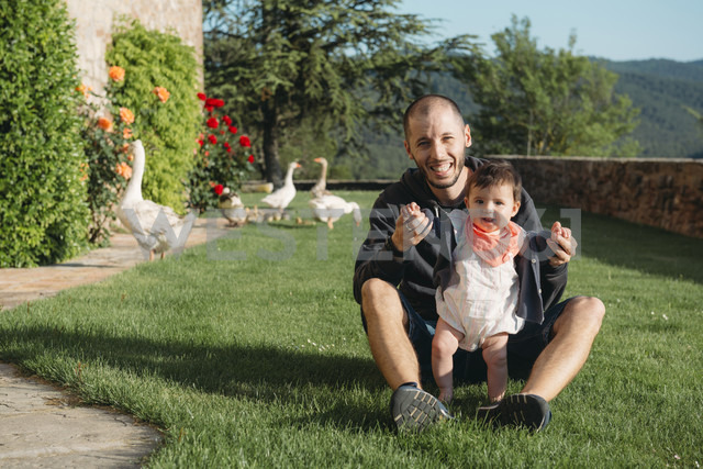 Cute baby girl walking on the grass with the help of her father and geese in the background - GEMF01672