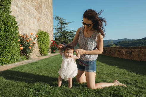 Cute baby girl walking on the grass with the help of her mother - GEMF01675