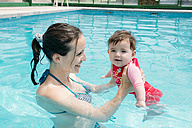 Cute baby girl learning to swim in the pool with her mother - GEMF01678