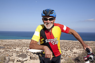 Spain, Canary Islands, Fuerteventura, smiling senior man with mountainbike - MFRF00847