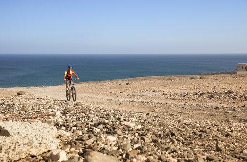 Spain, Canary Islands, Fuerteventura, senior man on mountainbike - MFRF00850