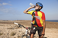 Spain, Canary Islands, Fuerteventura, senior man with mountainbike drinking from bottle - MFRF00853