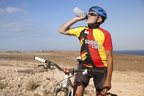 Spain, Canary Islands, Fuerteventura, senior man with mountainbike drinking from bottle - MFRF00853