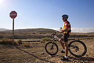 Spain, Canary Islands, Fuerteventura, senior man with mountainbike having a rest - MFRF00856
