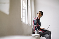 Smiling woman sitting at the window using laptop - KNSF01522