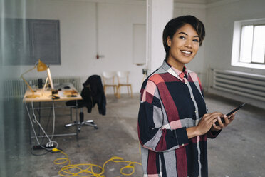 Smiling woman using tablet in empty office - KNSF01534
