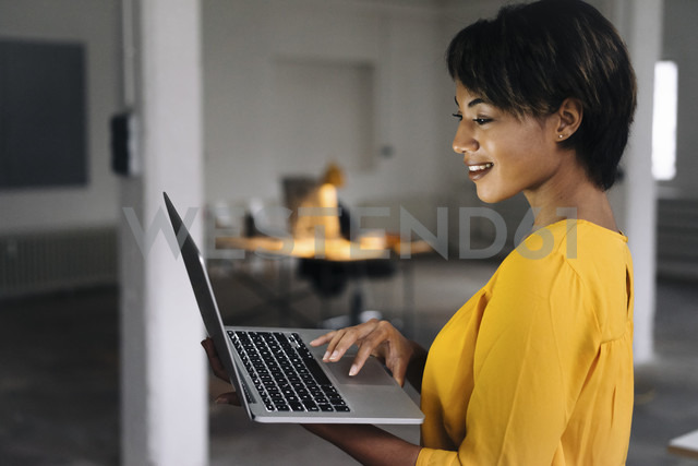 Smiling woman using laptop in empty office - KNSF01537 - Kniel Synnatzschke/Westend61