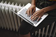 Woman sitting on heater using laptop - KNSF01540