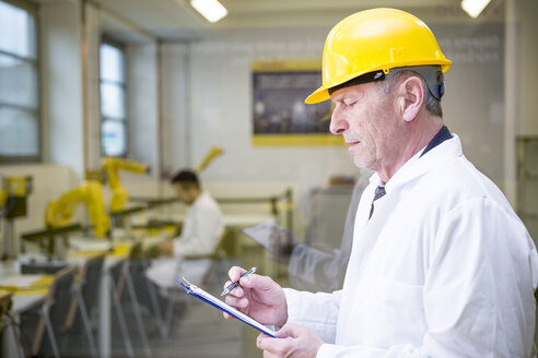 Engineer in factory with clipboard - WESTF23399