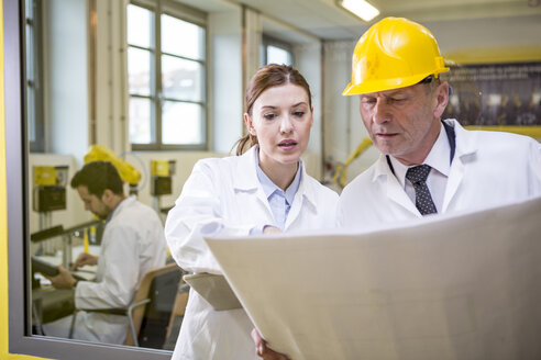 Two engineers in factory looking at plan - WESTF23402
