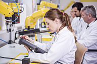 Engineers examining industrial robots - WESTF23405
